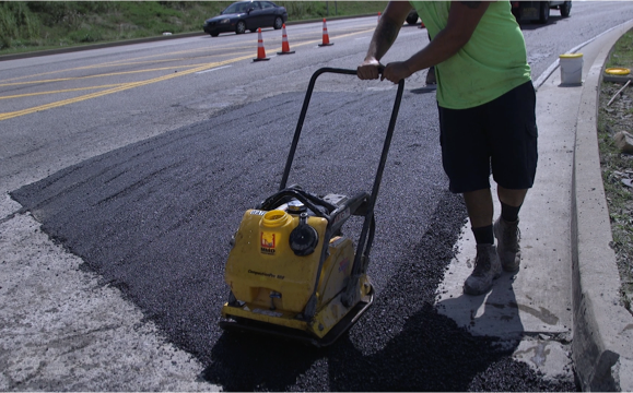 Smoothing the asphalt to finish the patching of the pothole.